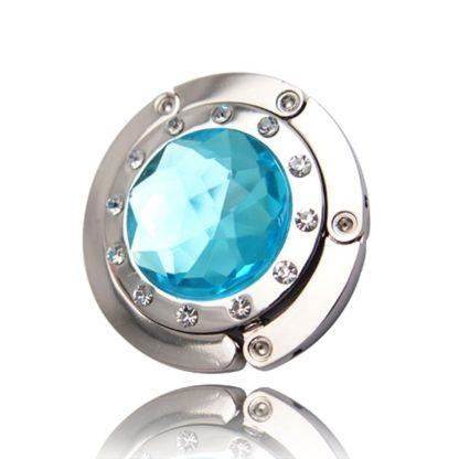 ljus turkos väskkrok eller väskhängare med stor strass kristall och små kristaller för att du ska kunna hänga din väska på bordet eller baren